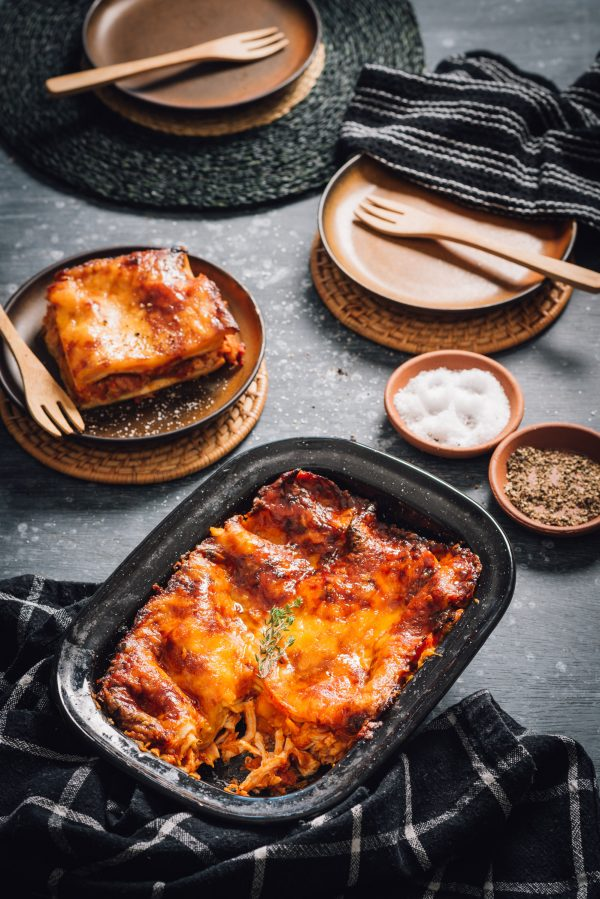 The roast chicken, sun-dried tomato and butternut lasagne being dished up onto two plates.