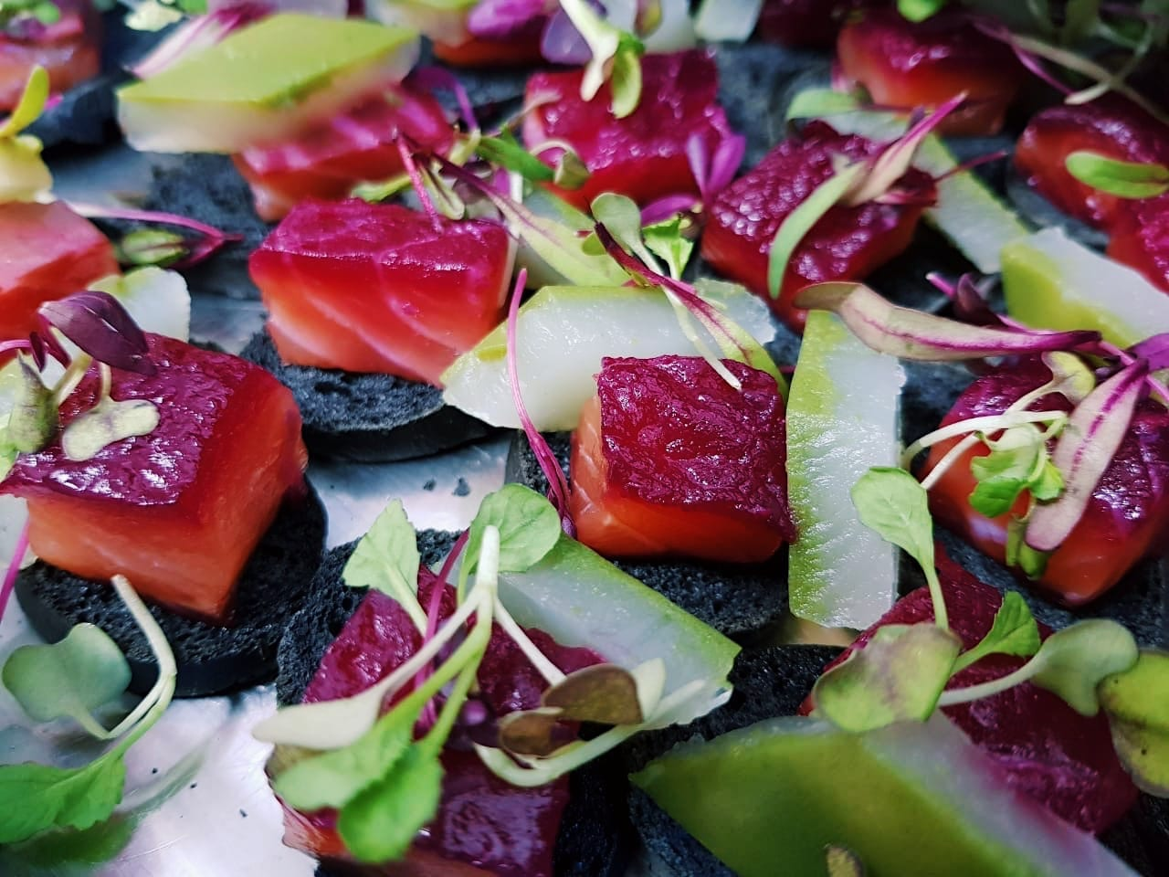 Gin cured salmon cubes on black croute with cucumber jelly. - DishFood