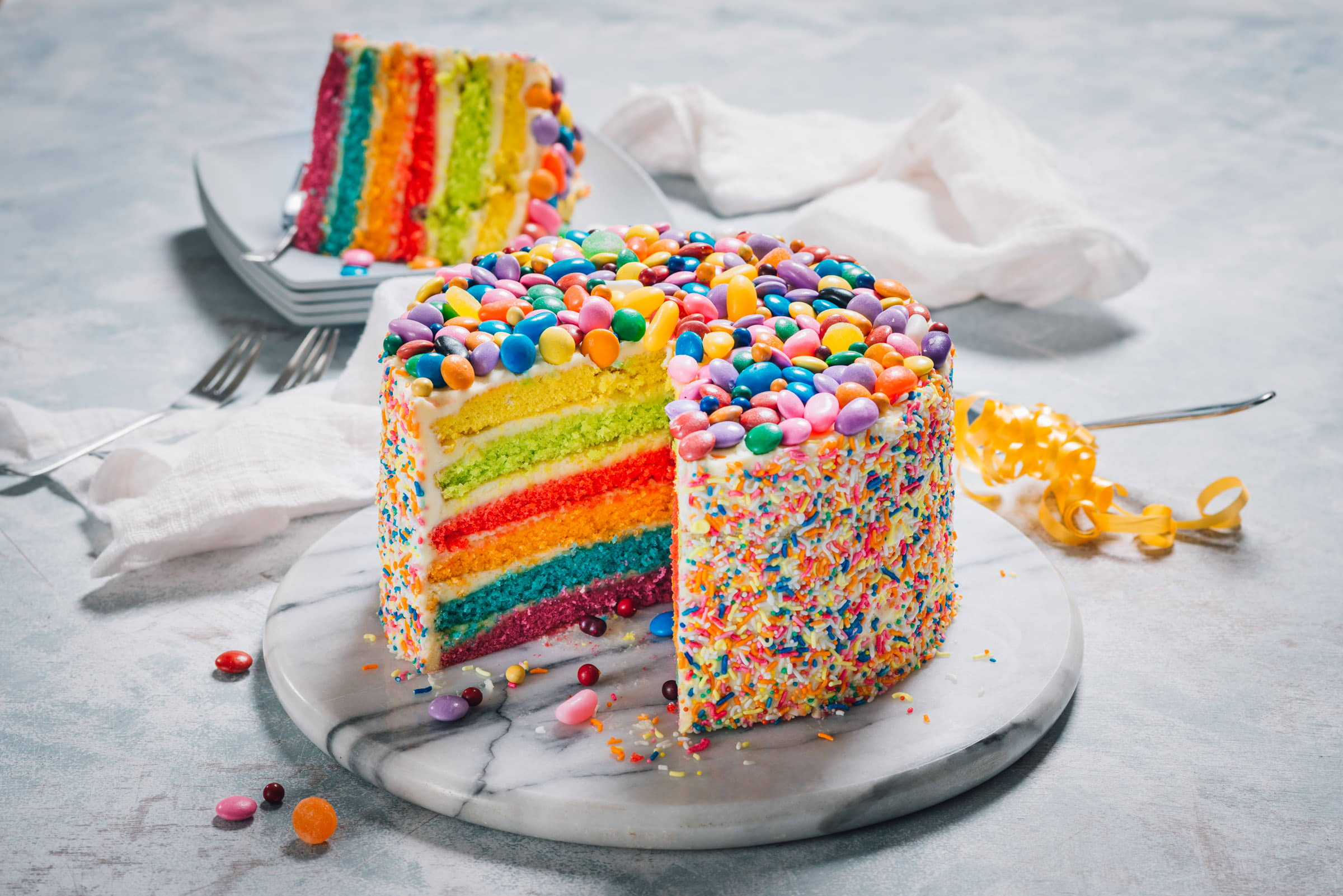 Our most frequently asked question might just be how to order this Rainbow Cake with Buttercream Icing and Candy Toppings!
